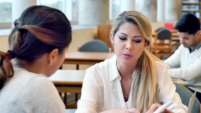 Focused female accountant talks with client about financial documents