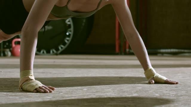 vídeos de stock, filmes e b-roll de focused female boxer doing push-ups - posição de combate