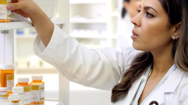 focused female pharmacist works on pharmacy inventory - label stock videos & royalty-free footage