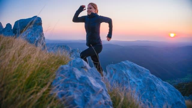 focused female runner exercising in nature, running to top of mountain - etereo video stock e b–roll