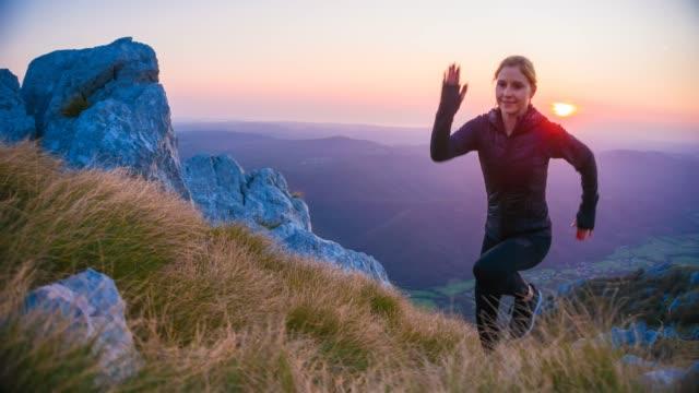 vidéos et rushes de concentré de coureur féminin au sommet de la montagne - qui monte