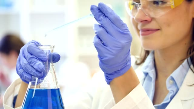 Focused female scientist drops liquid into a beaker
