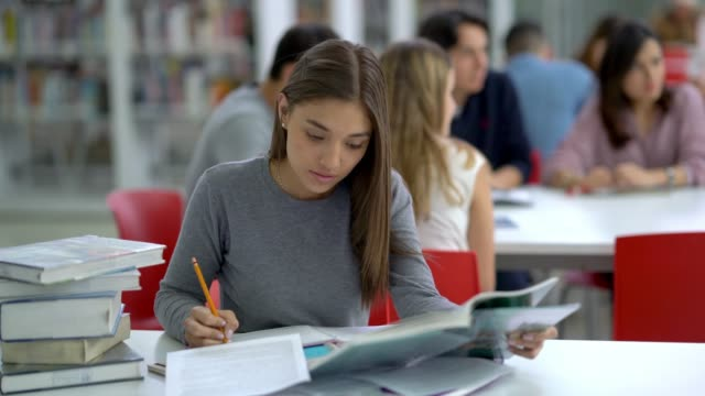 focused female young student at the library reading books and taking notes - educazione video stock e b–roll