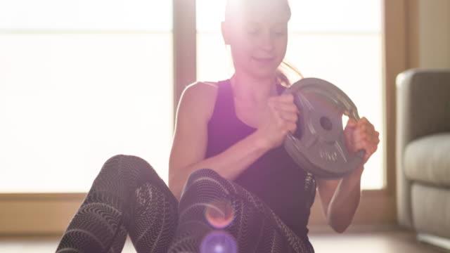 vídeos de stock, filmes e b-roll de mulher concentrada do ajuste que faz exercícios de torção russian ponderados para a construção de músculos abdominais - musculação