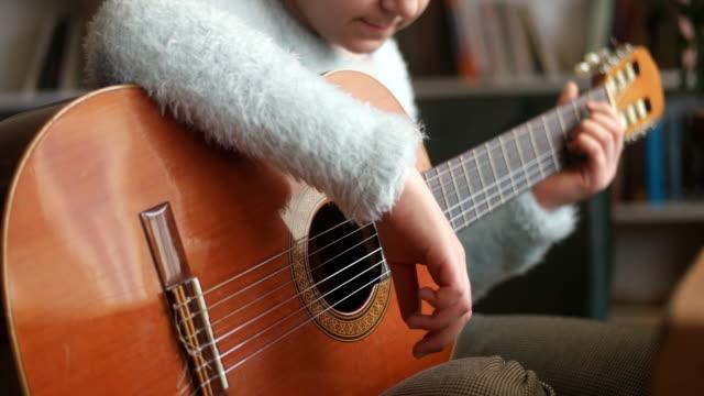 fokussierte mädchen selbstlernend gitarre spielen - gitarrist stock-videos und b-roll-filmmaterial