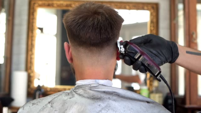 focused hairdresser cutting customer's hair using a electric razor - electric razor stock videos and b-roll footage
