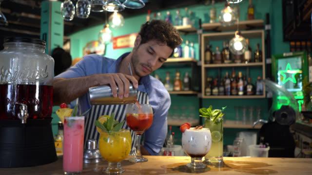 vídeos de stock, filmes e b-roll de barman masculino focalizado que prepara cocktail em uma barra - barman
