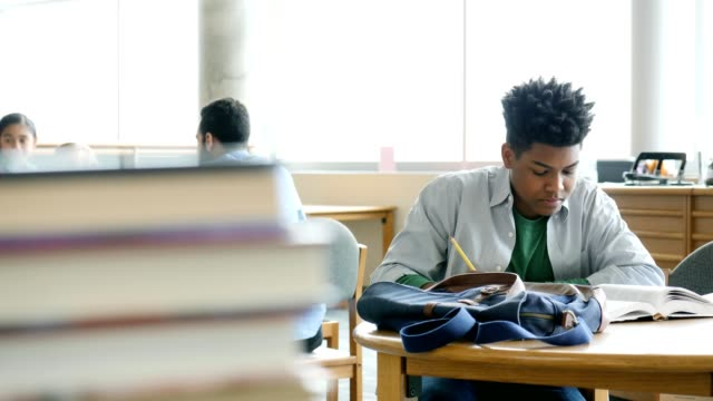 focused male high school student studies for test in school library - homework stock videos & royalty-free footage