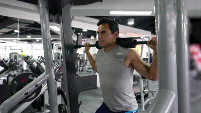 focused man at the gym working out legs and back with weights at the gym - exercise machine stock videos & royalty-free footage