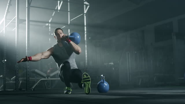focused man balancing with kettlebell at gym - weight training stock videos and b-roll footage