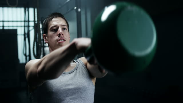 Focused man doing exercise with kettlebell at gym