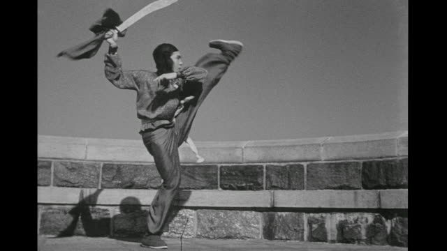 vídeos de stock e filmes b-roll de 1948 focused man (chao-li chi) performs martial arts and swings sword around his body outside alone - artes marciais