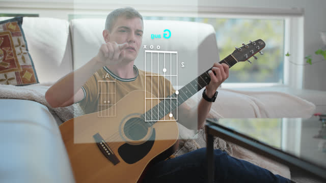 focused man uses his device to learn how to play guitar - internet of things stock videos & royalty-free footage