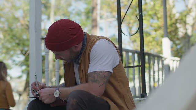 slo mo focused man writes in a journal outdoors - diary stock videos & royalty-free footage