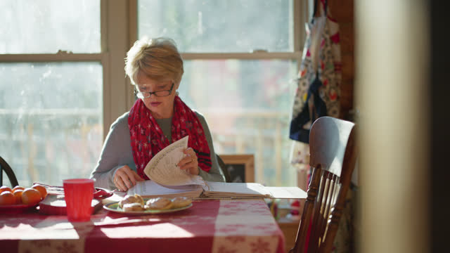 focused mature woman looks through cookbook in her kitchen - grandmother stock videos & royalty-free footage