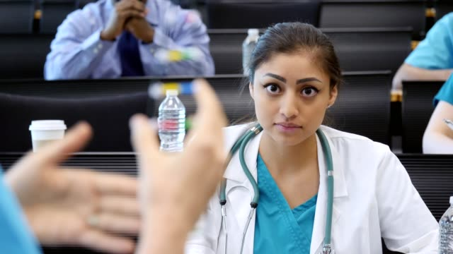 Focused medical student asks professor a question during chemistry class