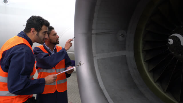 focused men checking the airplane's turbine while checking off a list on clipboard - examining stock videos & royalty-free footage