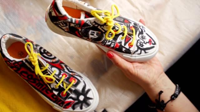 vidéos et rushes de l'artiste féminine de nouvelle vague concentrée peignent une basket dans différentes formes et couleurs - chaussures