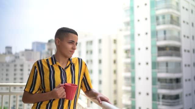 vídeos de stock, filmes e b-roll de pessoa não-binária focada na varanda do apartamento olhando para o lado - nostalgia