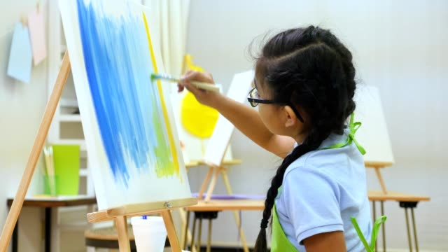 Focused preteen Asian girl paints in art class