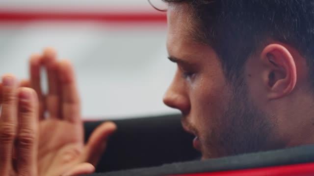 fokussierte racer gestikulieren beim sitzen im rennwagen - besorgtheit stock-videos und b-roll-filmmaterial