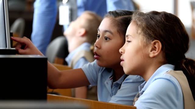 focused stem elementary schoolgirls study something on computer in computer lab - stem topic stock videos & royalty-free footage