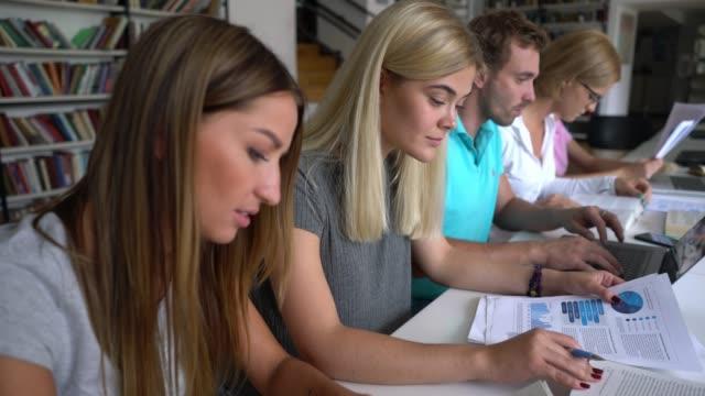 図書・文書・ノートパソコンを使った図書室での集中学習 - 公共図書館点の映像素材/bロール