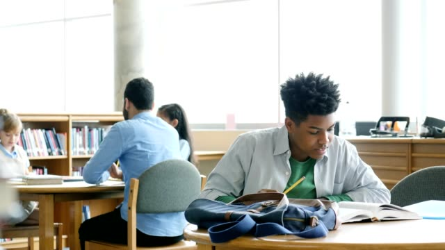 focused teenage boy studies in high school library - first day of school stock videos & royalty-free footage