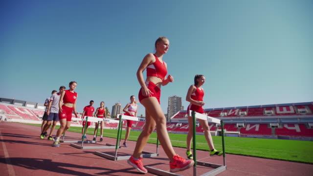 focused teenage runners hurdling - hurdle stock videos & royalty-free footage