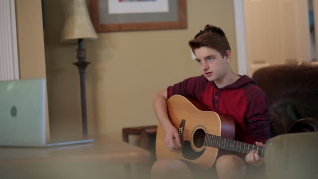 focused teenager learning to play the guitar via video call - one teenage boy only stock videos & royalty-free footage