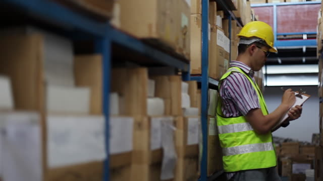 Focused warehouse male writing on clipboard in a warehouse