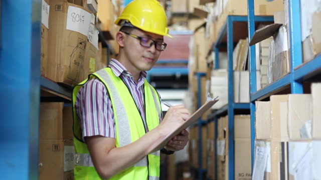 focused warehouse male writing on clipboard in a warehouse - delivery person stock videos & royalty-free footage