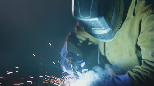 slo mo cu focused welder bonds metal with welding torch - steel worker stock videos & royalty-free footage