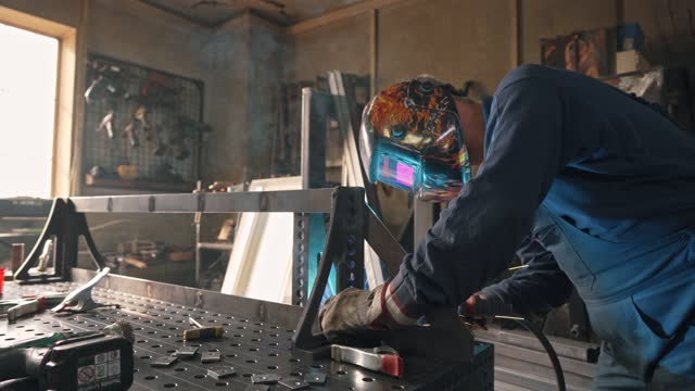 focused welder with a protective workwear welding a metal frame with a welding torch - welding helmet stock videos & royalty-free footage