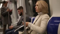 Focused woman browsing and typing messages on phone on way to work in modern metro
