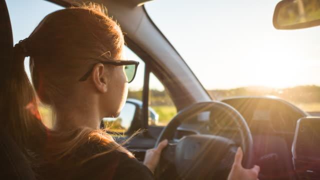 vídeos y material grabado en eventos de stock de centrada mujer conduciendo en carretera de tráfico pesado en día soleado - carro blindado