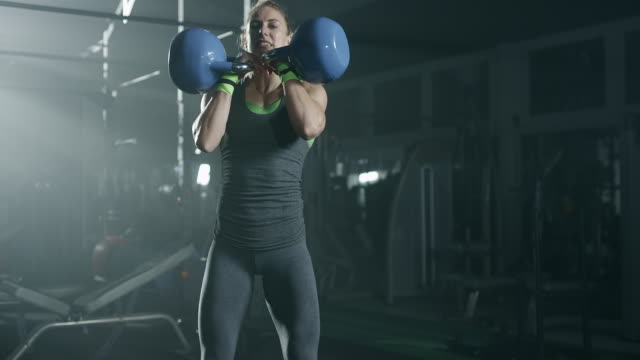 focused women doing exercise with kettlebell at gym - cura della persona video stock e b–roll