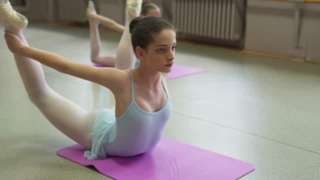 vídeos y material grabado en eventos de stock de bailarinas jóvenes enfocadas estirándose antes de la clase de ballet - 12 13 años