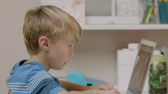 cu of focused young boy typing on a laptop to complete his schoolwork. - one boy only stock videos & royalty-free footage