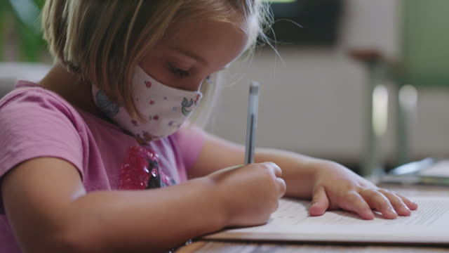 cu focused young girl wearing face mask sits at table, writes on form - only girls stock videos & royalty-free footage