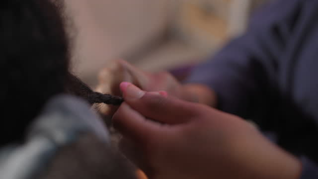 cu of focused young woman braiding her sister's hair - braided hair stock videos & royalty-free footage