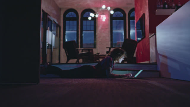 vidéos et rushes de focused, young woman lying on the floor as she works on her laptop late into the night - petit bureau