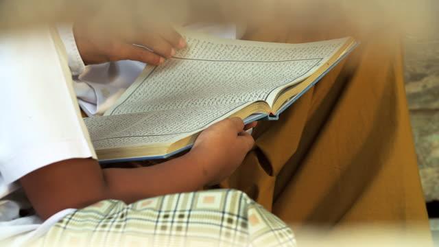 focusing hand of muslim teacher and children reading koran.illustrate of muslim education activity. - koran stock videos & royalty-free footage