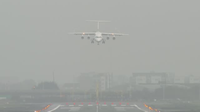 fog causes travel disruption at london airports england london london city airport wind sock and buildings surrounded by fog plane coming in to land... - itv london tonight weekend点の映像素材/bロール