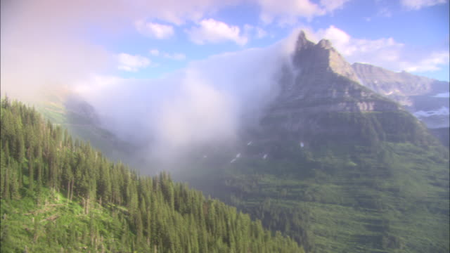 fog clings to mountain peaks in glacier national park. - glacier nationalpark stock-videos und b-roll-filmmaterial