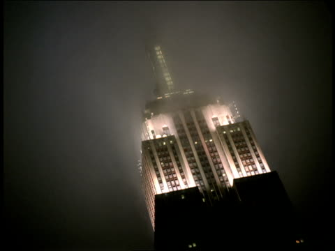 Fog drifts around the top of an illuminated Empire State Building.
