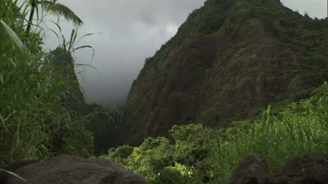 fog drifts behind mountains near a cascading waterfall in iao valley on hawaii's maui island. - maui stock videos & royalty-free footage