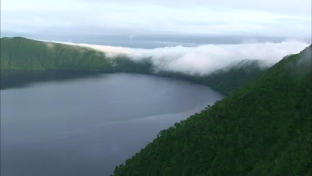 Fog drifts over a ridge surrounding Lake Mashu.