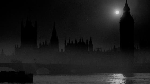 fog drifts over boats on the river thames near the silhouetted houses of parliament at night. - victoria tower stock videos & royalty-free footage