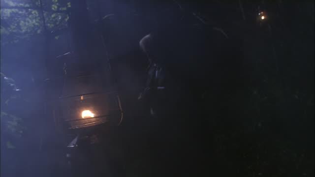 fog drifts past a lantern where a man sits smoking a cigar. - lantern stock videos & royalty-free footage